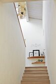 Narrow staircase and view into attic interior with pendant lamp suspended from white-painted wooden ceiling