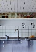 Detail of kitchen counter with stainless steel sink, white wall tiles and shelf of storage jars
