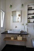 Modern washstand with marble countertop basin below mirror and two sconce lamps in corner of bathroom
