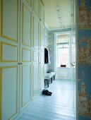 Narrow hallway with fitted cupboards painted white and yellow leading to open-plan dressing room