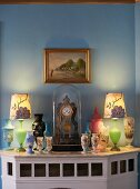 Various painted vases and table clock under glass cover on wood-clad fireplace below gilt-framed landscape on wall painted pale blue