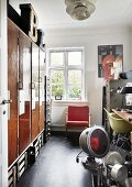 Open door with view into workshop; vintage lamps on floor, old fitted cupboards and retro armchair below window