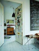 Retro Klapptisch neben offener Flügeltür und Blick ins Jugendzimmer, Skateboard auf weißem Dielenboden in Altbauwohnung