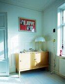 Tischleuchte Pilzlampe auf Fifty Sideboard aus Holz in Zimmerecke vor weiss lackierter Holzwand