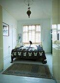 Blick ins Schlafzimmer einer Altbauwohnung mit minimalistischem Flair, französisches Bett und folkloristische Tagesdecke vor Fenster mit Lamellen Jalousie