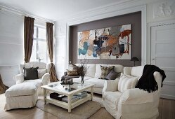 Coffee table with glass top and white wooden frame amongst sofa set and large, modern artwork on wall in grand interior