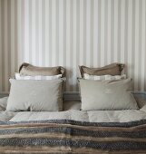 Stacked pillows in coordinated colours on French bed against wall with striped wallpaper in traditional bedroom with subdued colour scheme