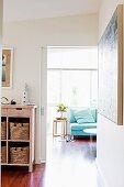Blick durch offene Schiebetür in lichtdurchfluteten Wohnraum auf Sofa am Fenster