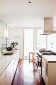 weiße Küchenzeilen gegenüberliegend mit Dunstabzug an Decke, im Hintergrund Terrassentüren mit Lamellenfenster