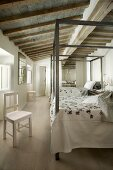 Twin four-poster beds with metal frames in long, rustic bedroom with wood-beamed ceiling