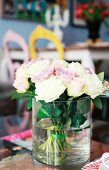 Bouquet of white and pale lilac roses in cylindrical glass vase; dining area in blurred background