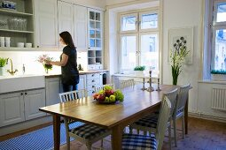 Kitchen-dining room with wooden dining table and white chairs with gingham seat cushions; woman standing at kitchen counter