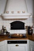 Country-house-style fitted kitchen with masonry extractor hood above ceramic hob