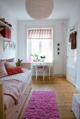 Pink flokati rug on wooden floor next to comfortable bed in child's bedroom