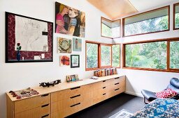 Sideboard with drawers below drawings on bedroom wall and ribbon windows with garden view