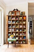 Flea-market finds on old wooden shelves against wall, fruit bowl on retro stool on wooden floor in traditional interior