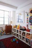Modern art above open-fronted shelves in child's bedroom