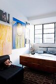 Retro sideboard at foot of bed in bedroom with industrial window and collection of artworks on wall
