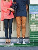Legs and bodies of young couple standing outside front door holding dog