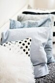 Row of patterned and plain scatter cushions on bench