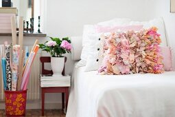 Scatter cushions with ruffles in shades of pink on couch with white blanket