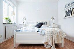 White wooden bed in rustic bedroom