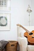 Guitar on armchair in front of retro standard lamp in corner