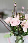 Bouquet of pastel roses with flowering branches