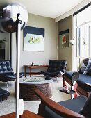 Black leather easy chairs around coffee table, retro standard lamp and modern still-life painting on wall in lounge area