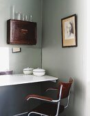 Retro armchair at white floating tabletop below antique wooden cabinet mounted on wall
