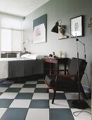 Retro standard lamp next to fifties-style armchair with black upholstery on chequered floor in bedroom painted grey