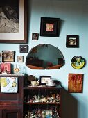 Open-fronted, dark wood, vintage-style shelving below pictured and semicircular mirror on painted wall