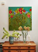 Vases of flower and white pillar candles on candlesticks on wooden chest of drawers below painting of flowers on wall