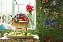 Animal figurine behind dish of various green fruits below window in wall tiled in mosaic of green tile fragments