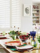 Colourful, patterned place settings, full glasses of water and glass bowl of fresh strawberries on table