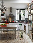 Transparent plastic chairs with colourful stripes on backrests around wooden table in white, country-house kitchen