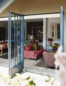 View from terrace through open lattice doors into interior with antique sofa and armchairs