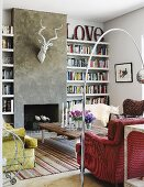 Red armchair below retro arc lamp and rustic coffee table in lounge area opposite open fireplace below stylised hunting trophy on grey rendered wall