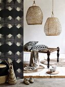 Natural materials and modern, African print curtain with graphic, black and white pattern, basketwork lampshades and bench with turned legs and fabric strap seat