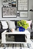 White and grey seating area with sofa, royal blue glass vase as focal point on DIY coffee table on castors and gallery of pictures in background
