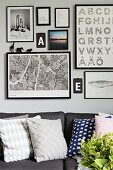 Gallery of framed pictures and typefaces above grey sofa with scatter cushions