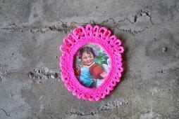 Vintage Bildnis eines jungen Mädchens mit gehäkeltem Rahmen in pinkfarbener Neonfarbe an Betonwand