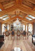 Essplatz mit langer Tafel auf edlem Parkettboden vor offener Küche im ausgebauten Dachgeschoss eines modernen Chalets