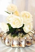 White roses in mercury glass vase