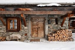 Winter atmosphere - rustic stone house with firewood stacked against facade