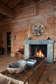 Rough bowl made of natural material on rustic wooden coffee table in front of open fire in cabin interior
