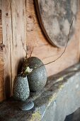 Flowering twigs in stone vase and egg-shaped stone on vintage shelf