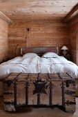 Simple bedroom in cabin - double bed with white bed linen and rustic wooden trunk with wrought iron fittings