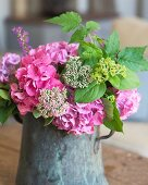 Summery bouquet of garden flowers with pink hydrangeas in vintage metal jug