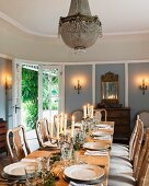 Lit candles on festively-set table and walls in dining room with traditional, country-house atmosphere
